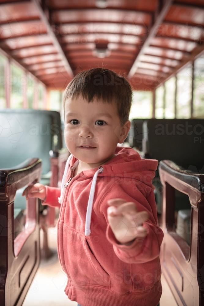 Excited 2 year old mixed race boy cheerfully rides the Walhalla historic train - Australian Stock Image