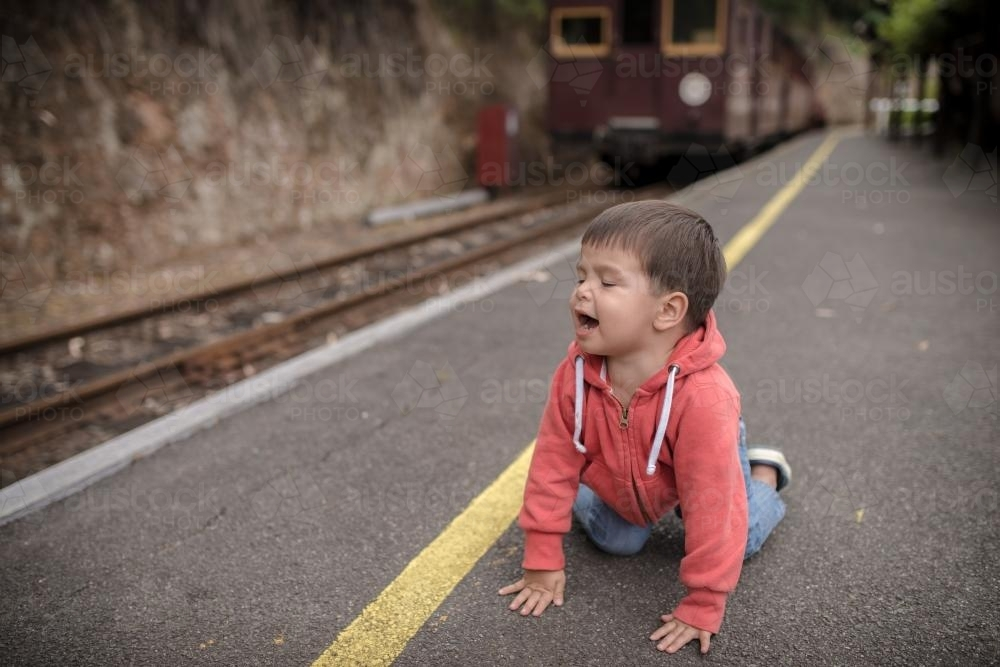 Excited 2 year old mixed race boy on hands and knees an a train platform - Australian Stock Image