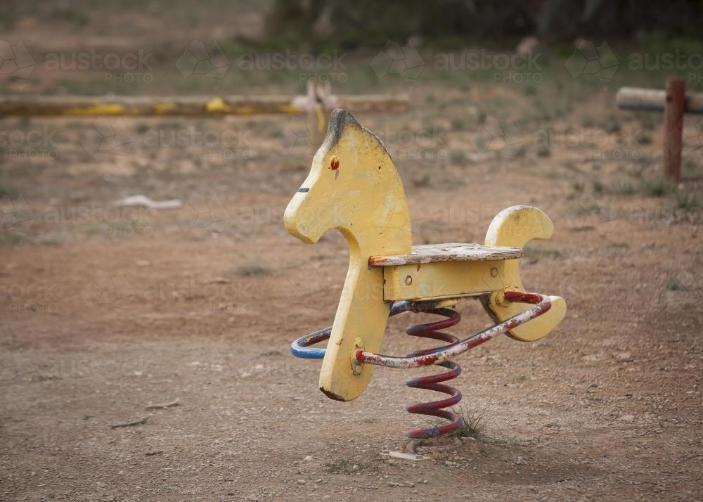 Faded yellow rocking horse at park playground - Australian Stock Image