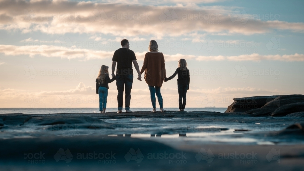 Family of four silhouette looking out at beach - Australian Stock Image