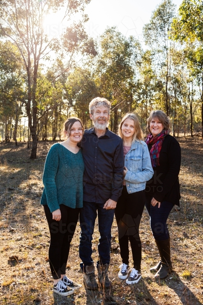 Family with teen and adult daughters standing together in paddock - Australian Stock Image