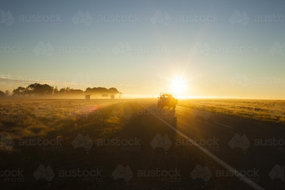Farm ute driving into sun on country highway - Australian Stock Image