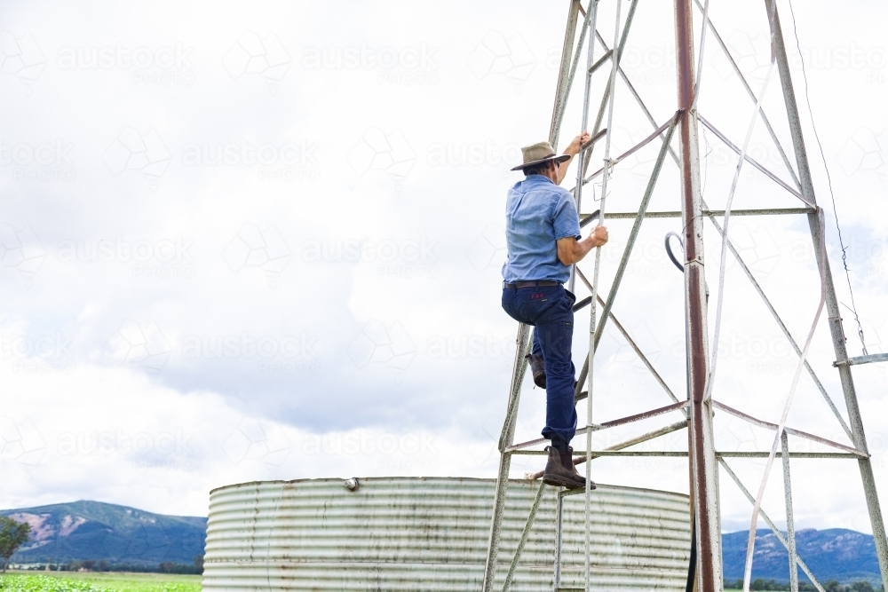Farmer climbing up farm windmill to check and repair pump - Australian Stock Image
