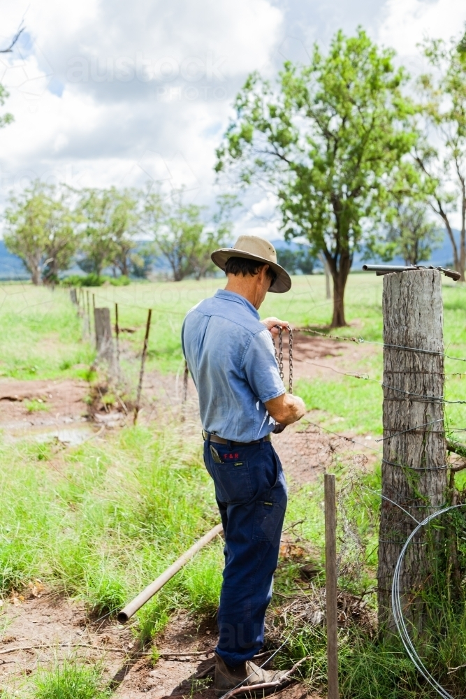 Farmer repairing fence so neighbours stock can't get through - Australian Stock Image
