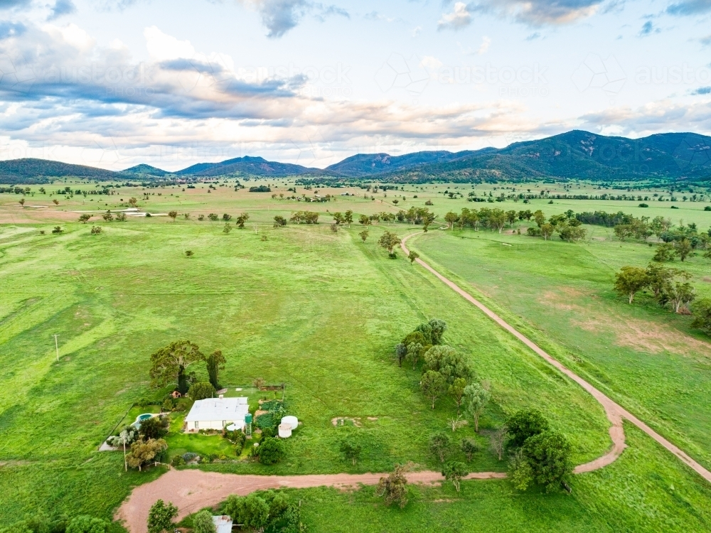 Farmhouse at the end of long driveway and green farm paddocks at dusk - Australian Stock Image