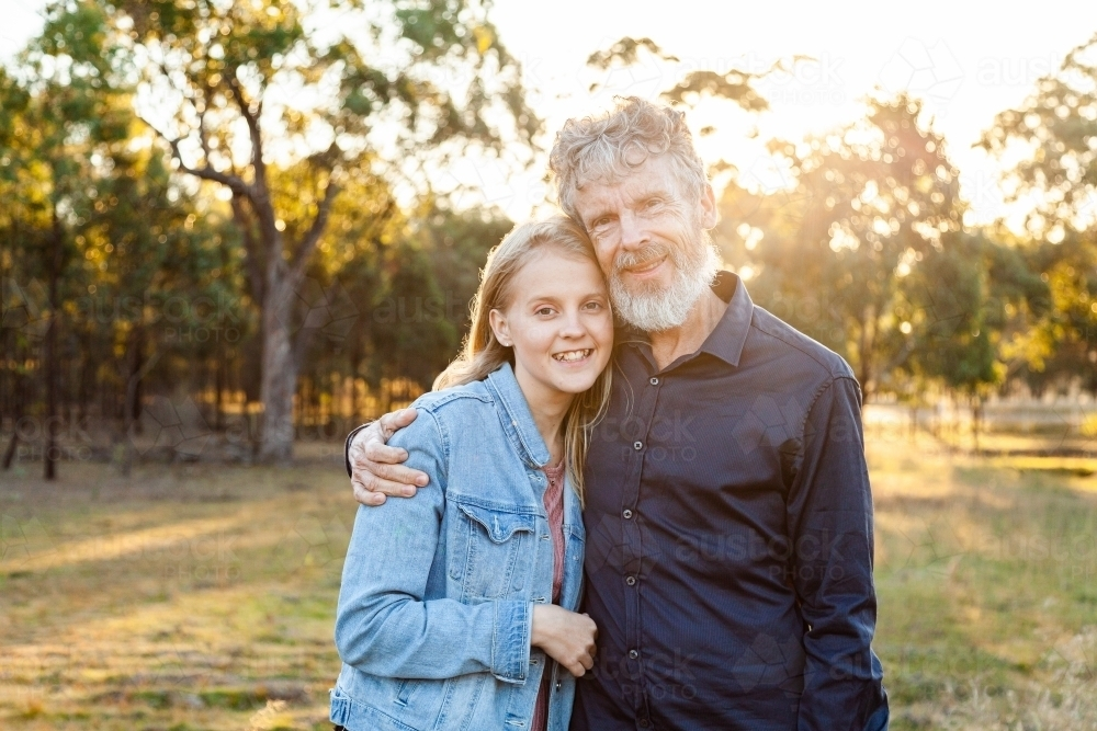 Father and daughter hug together in paddock with copy space - Australian Stock Image