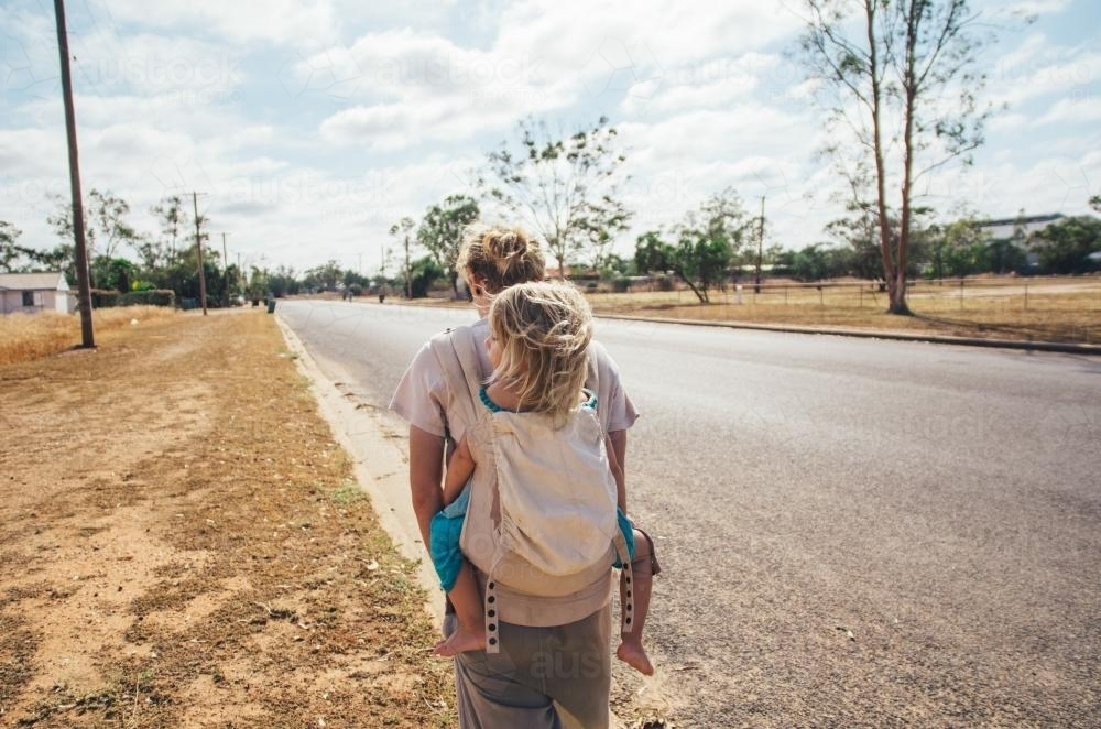 Father and daughter walking on rural streets - Australian Stock Image