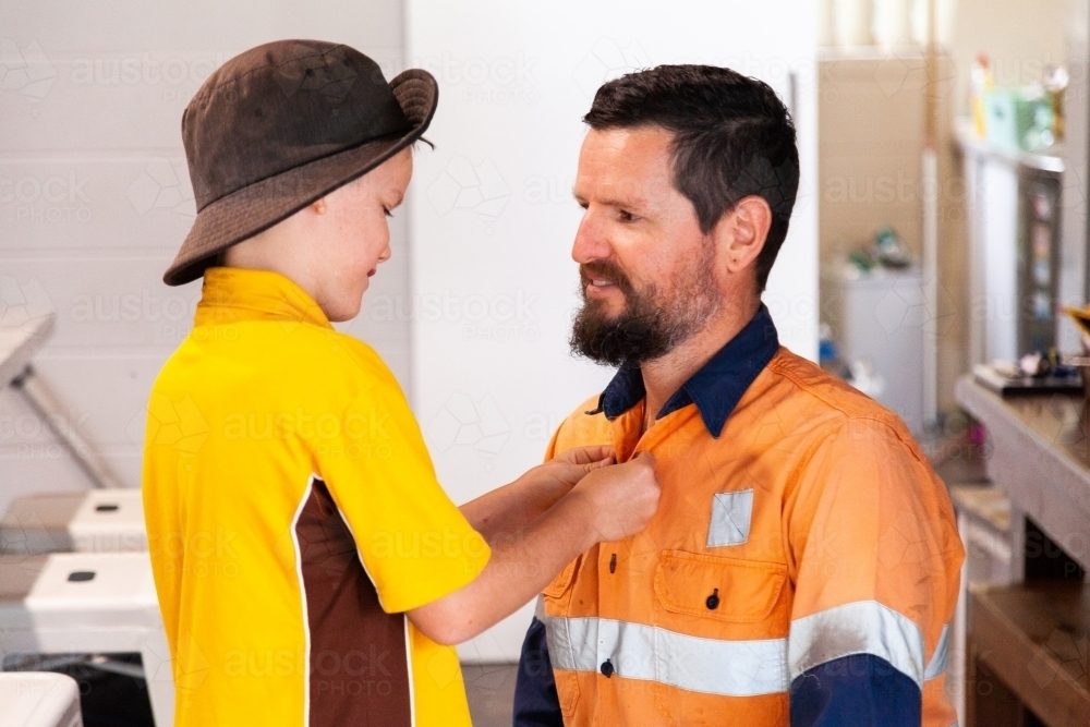 Father and son helping each other do up shirt buttons before work and school - Australian Stock Image