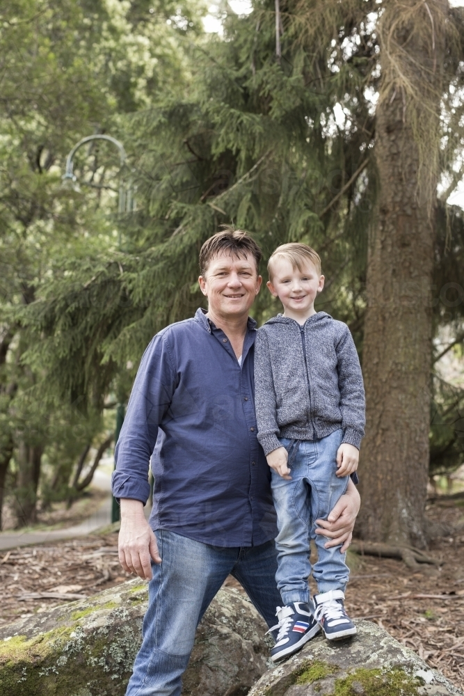Father and son standing on rocks, smiling for camera - Australian Stock Image