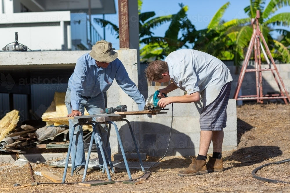 Father and son working together on a building project - Australian Stock Image