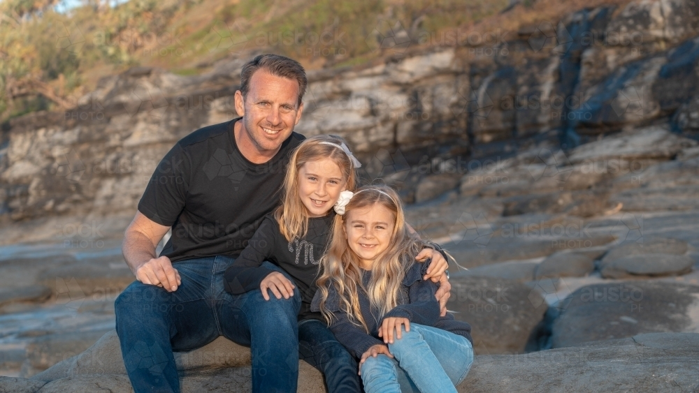 Father and young daughters looking at camera - Australian Stock Image