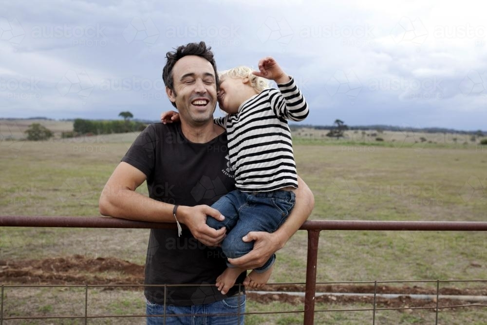 Father and young son laughing together on old gate on rural farm - Australian Stock Image