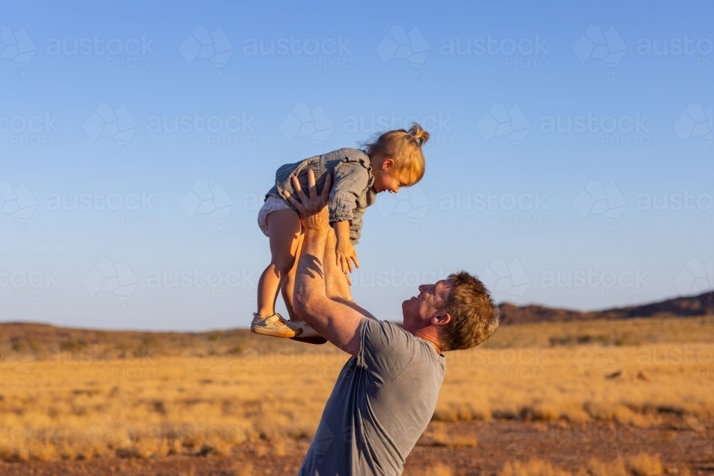 father holding toddler up in the air - Australian Stock Image