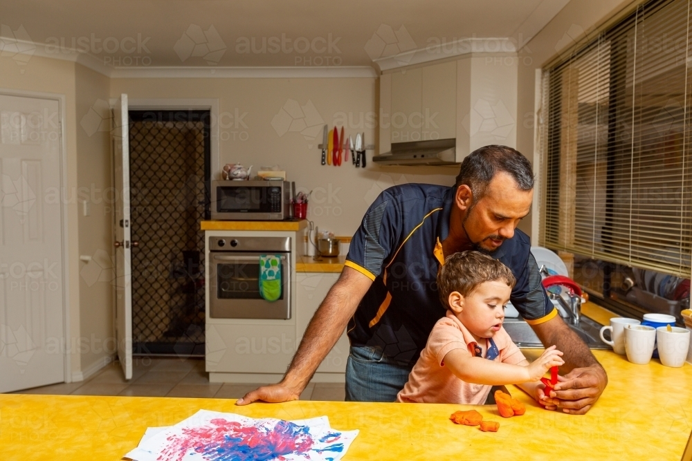 father playing with his young son in the kitchen - Australian Stock Image