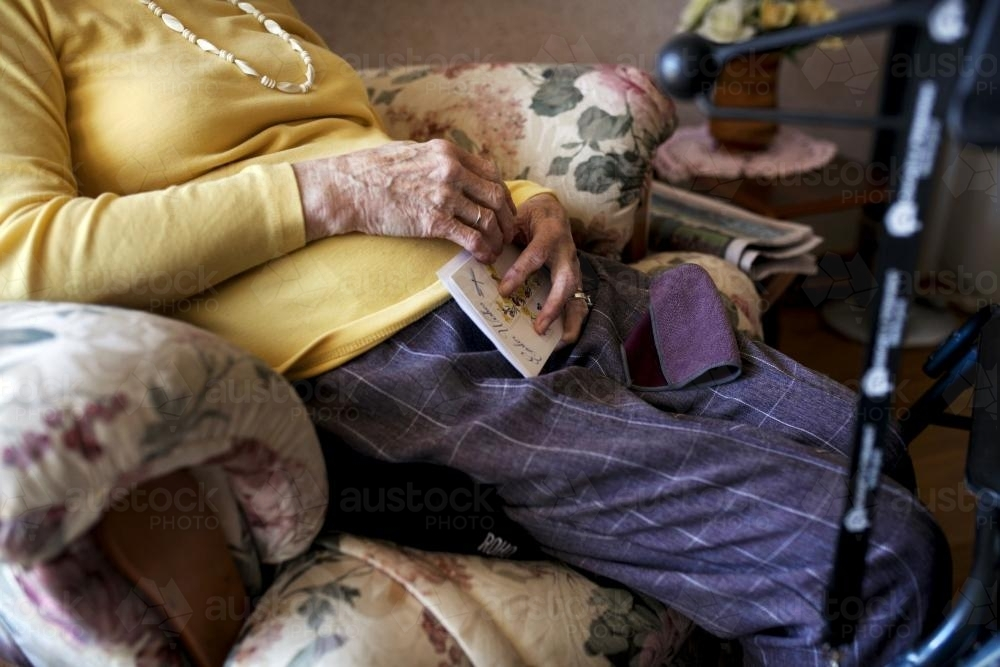 Female retirement village resident sitting in an arm chair - Australian Stock Image