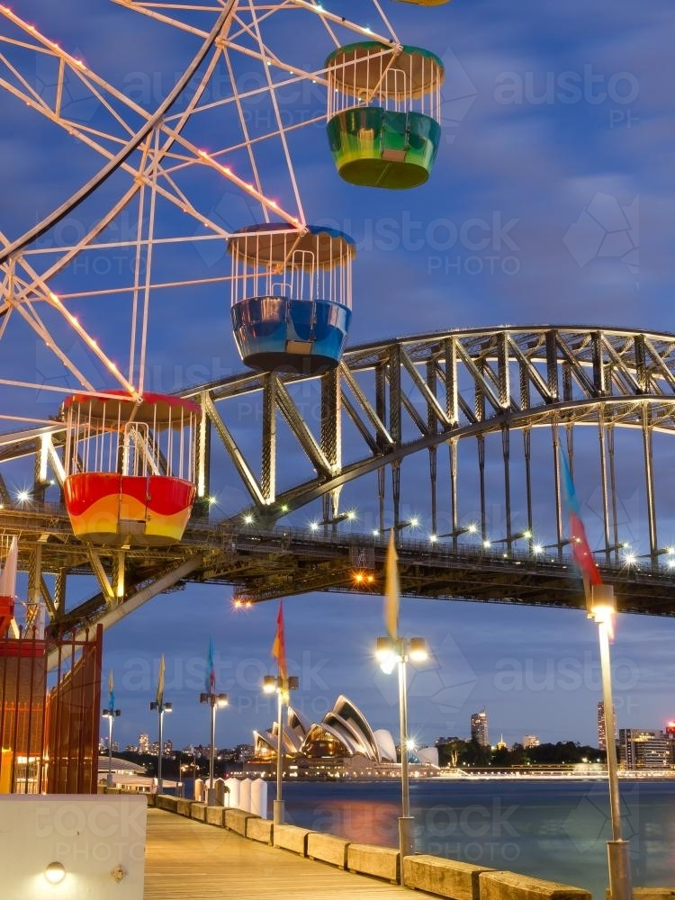 Ferris wheel cabs against a blue sky with Harbour Bridge in the background - Australian Stock Image