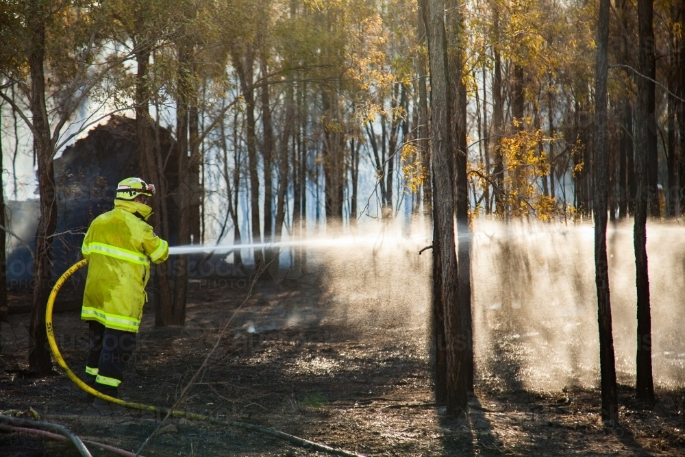 Fire and rescue fireman spraying water on a fire from hose - Australian Stock Image