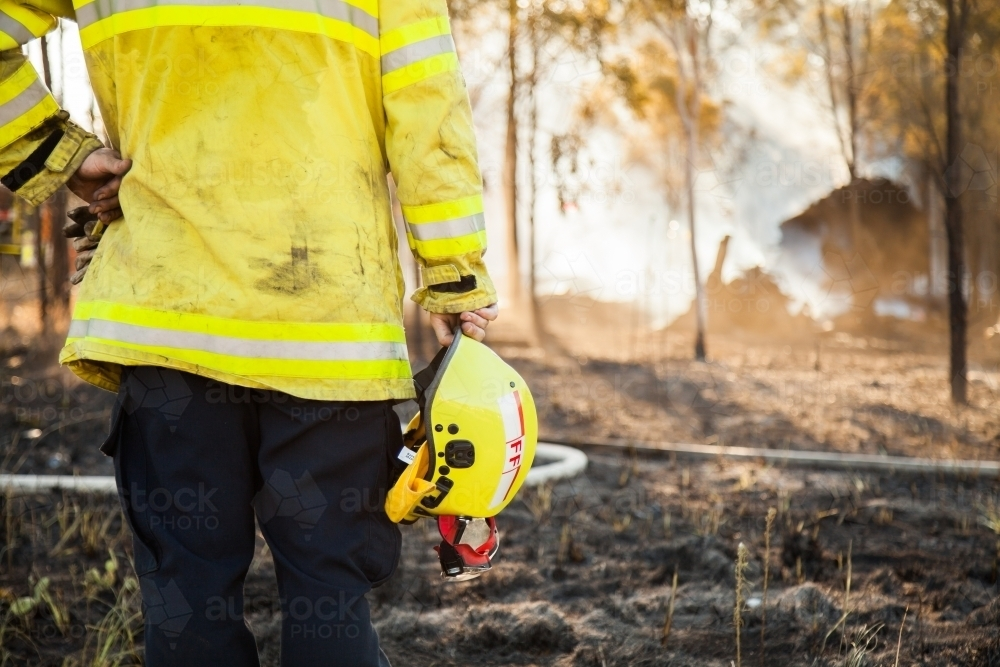 Fire fighter standing beside burnt grass holding safety helmet in hand - Australian Stock Image