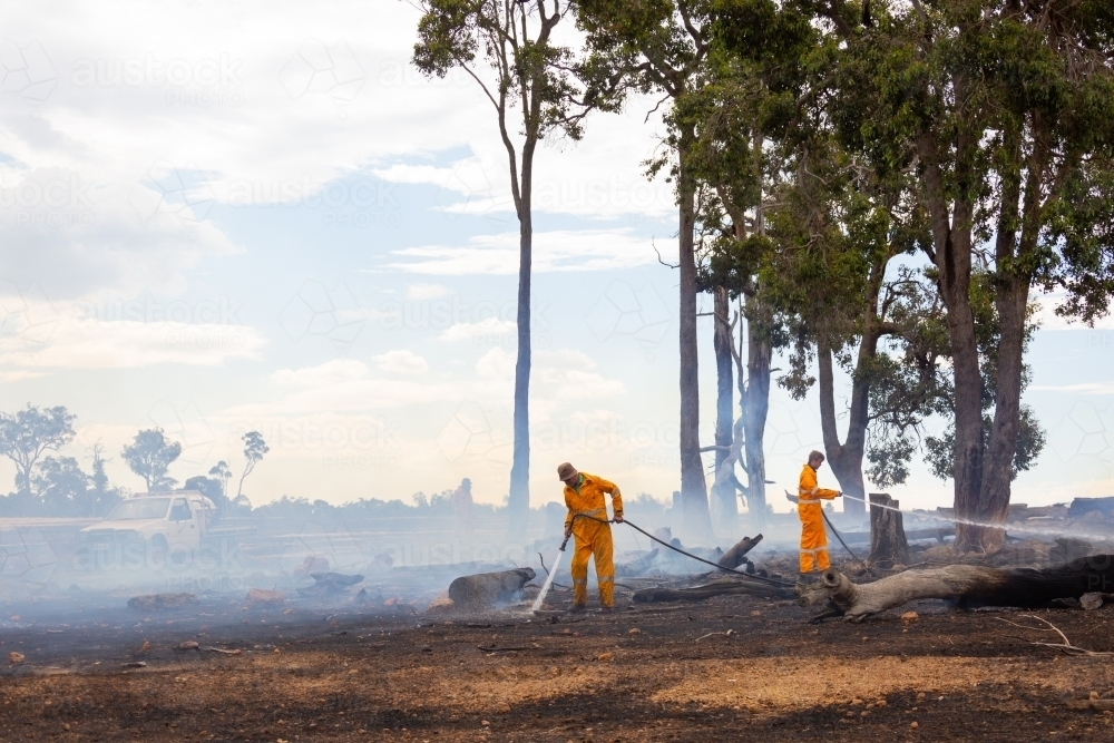 firefighters in smoke using hoses to spray water on burnt logs after a fire - Australian Stock Image