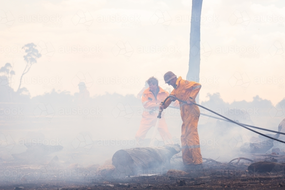 firefighters using hoses to spray water on burnt logs after a fire - Australian Stock Image