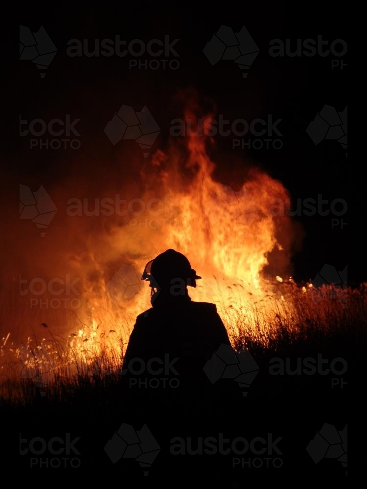 Firemen fighting a grass fire at night silhouetted against the flames - Australian Stock Image