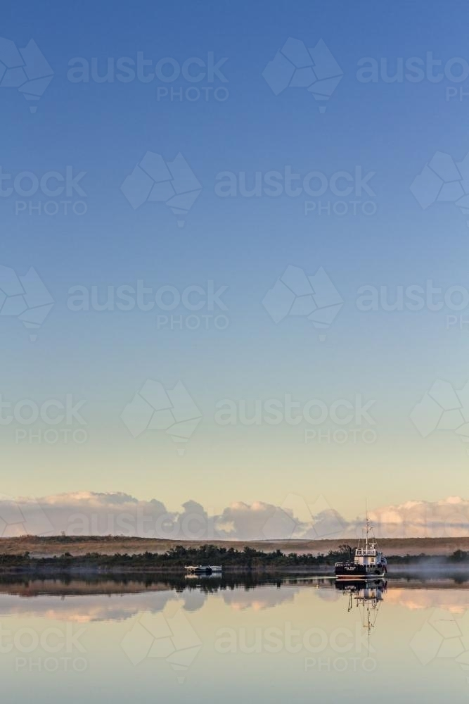 Fishing boat on calm waters with reflection - Australian Stock Image