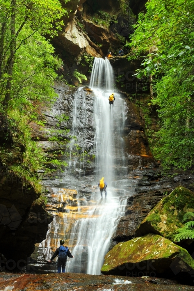 Five people abseiling down and through the waterfall at Empress Falls in the Blue Mountains of NSW - Australian Stock Image