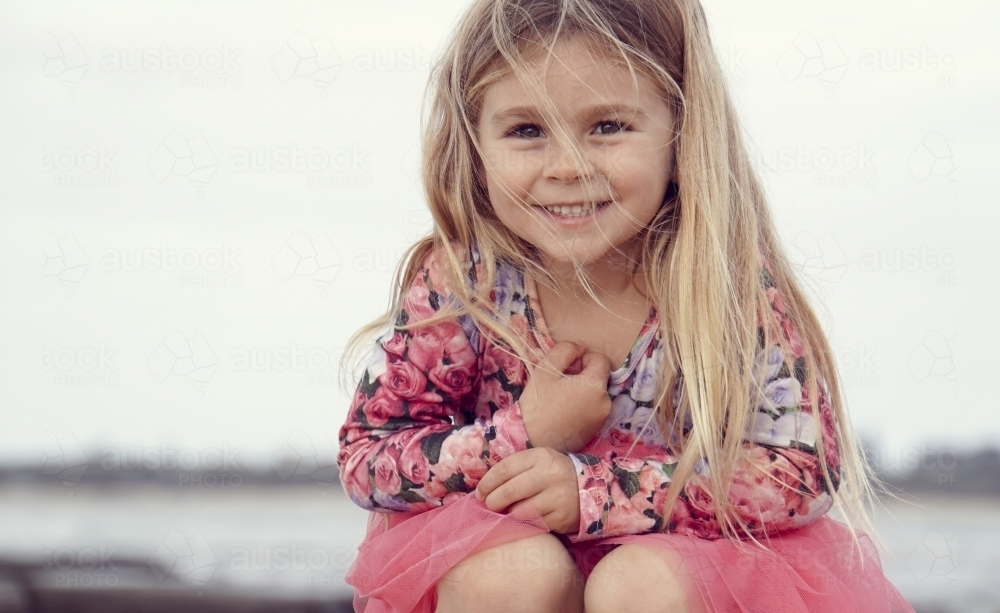 Five year old sitting smiling at camera - Australian Stock Image