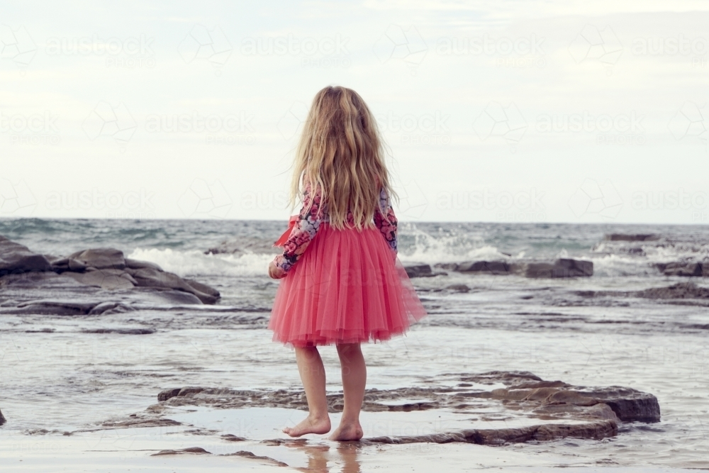 five year old walking along beach looking away - Australian Stock Image