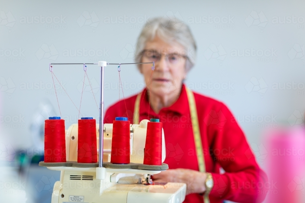 focus on red thread with elderly lady blurred behind sewing machine - Australian Stock Image