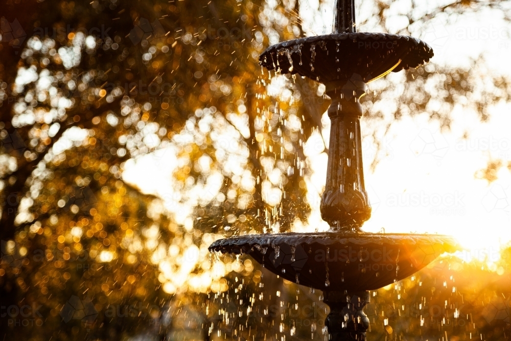 Fountain with water droplets in golden sunset light - Australian Stock Image