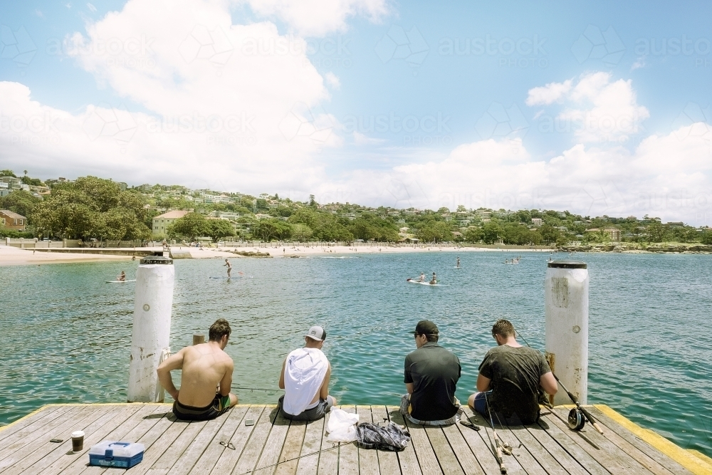 Friends / boys sitting on a pier fishing on a beautiful day - Australian Stock Image