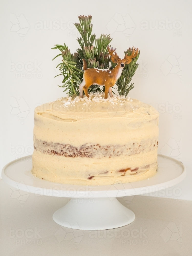 Image Of Frosted Christmas Cake With Mini Trees And Deer Decoration