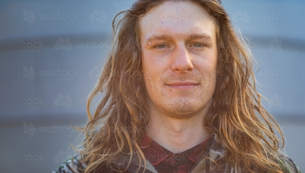 full face of young bloke with long hair and facial piercings - Australian Stock Image