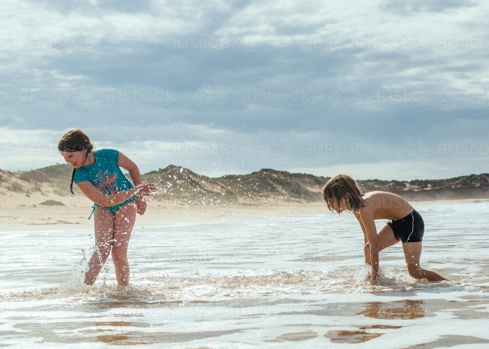 Girl and boy splashing in ocean - Australian Stock Image