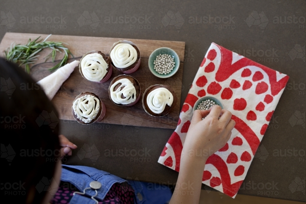 Girl decorating cupcakes in kitchen at home - Australian Stock Image