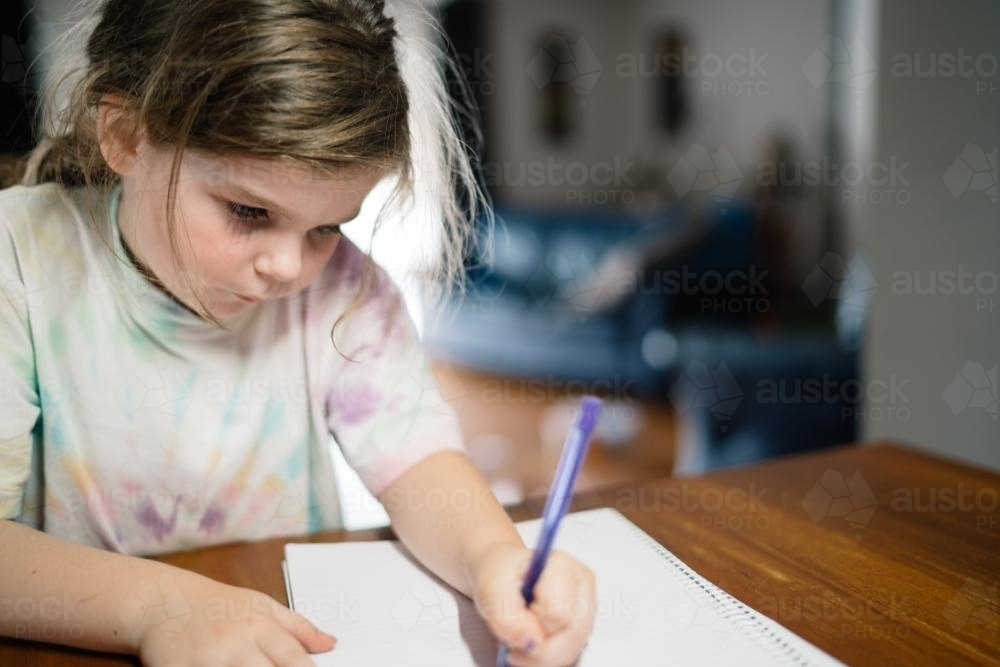Girl Drawing with a Purple Pen - Australian Stock Image