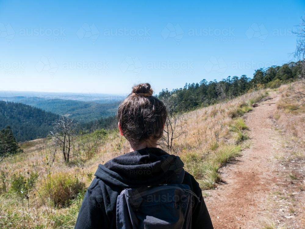 Girl from behind hiking in the mountains - Australian Stock Image