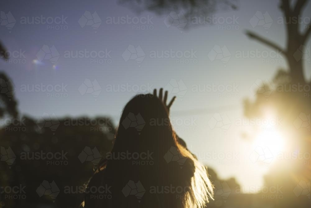 Girl from behind reaching out to setting sun - Australian Stock Image