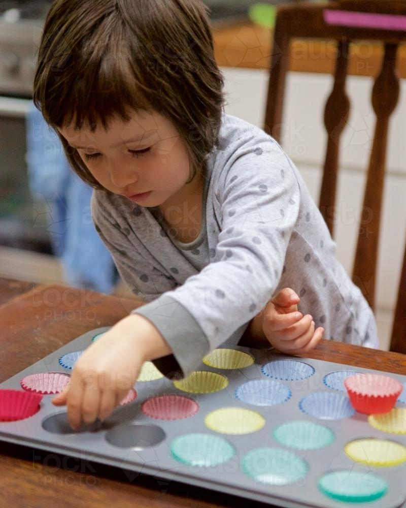 Girl helping bake cupcakes by putting patty pans in a baking tin - Australian Stock Image