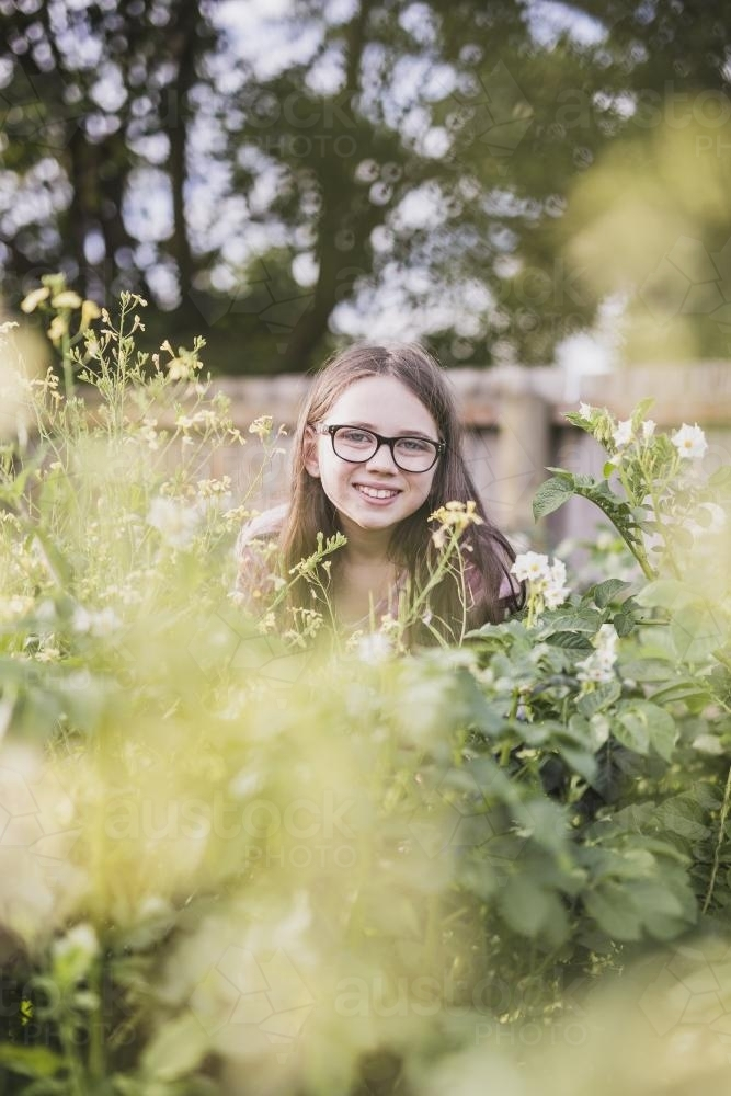 Girl hiding in potato plants - Australian Stock Image