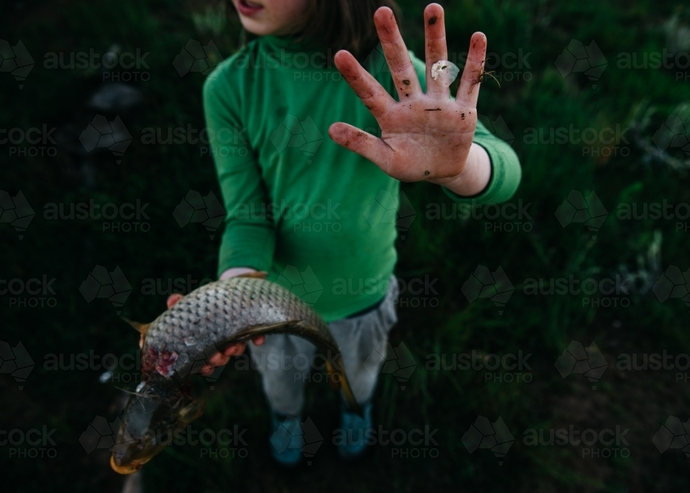 Girl holding carp showing dirty hand - Australian Stock Image