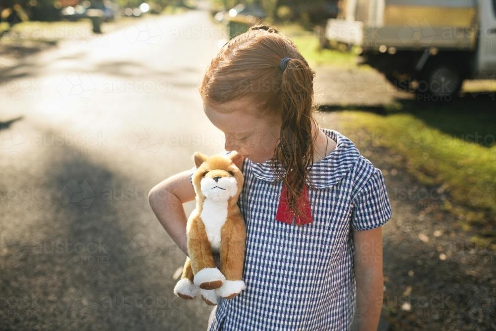 Girl hugging a toy dog on the street - Australian Stock Image