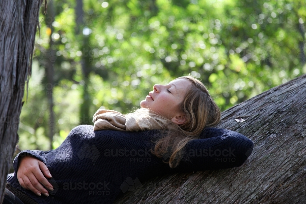 Girl leaning back on tree - Australian Stock Image