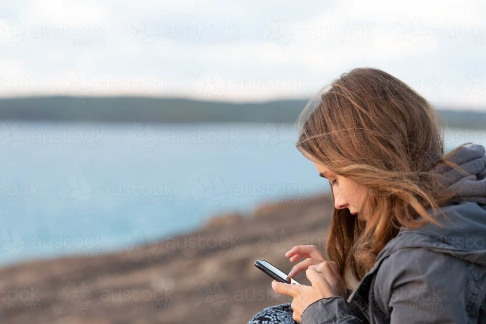 Girl looking at smartphone near the sea - Australian Stock Image