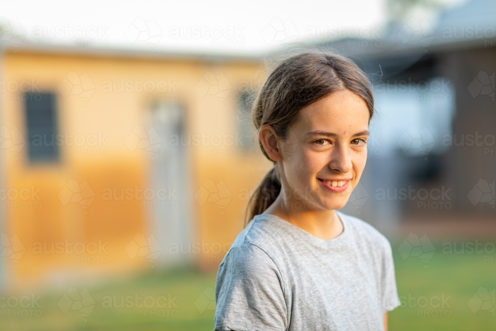 girl outside in yard with rustic building blurred in background - Australian Stock Image