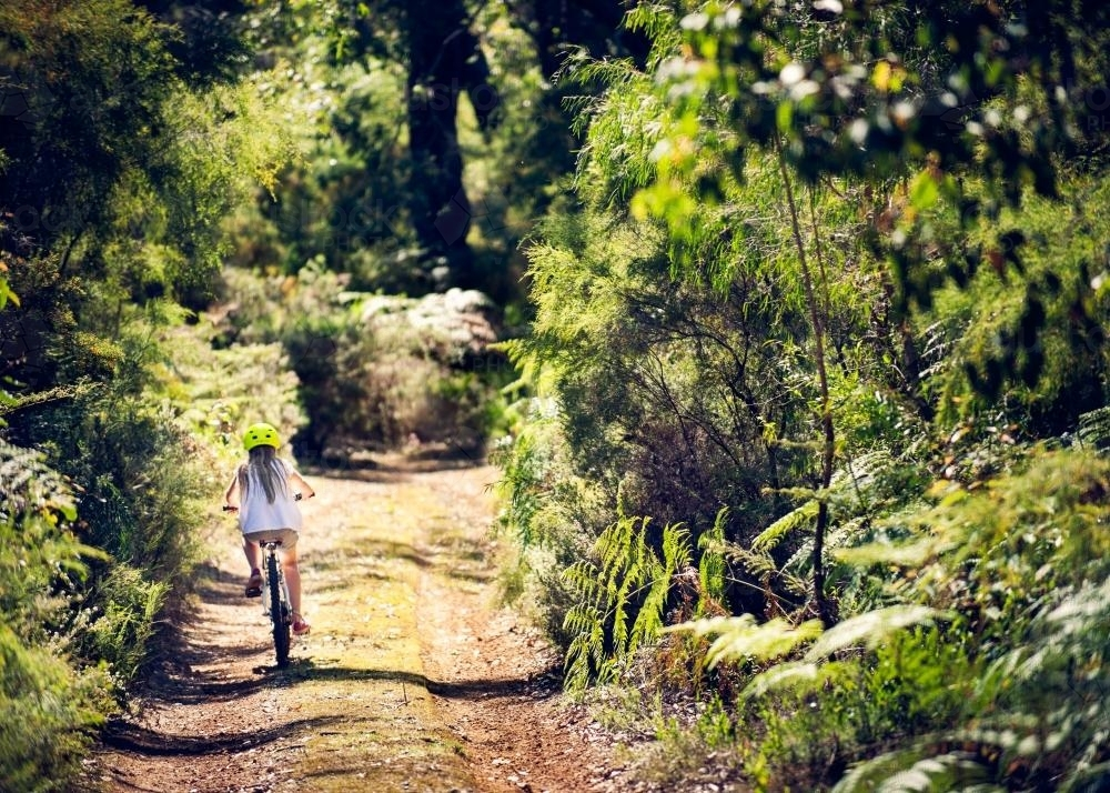 Girl riding a bike down a dirt road surrounded by dense bush - Australian Stock Image