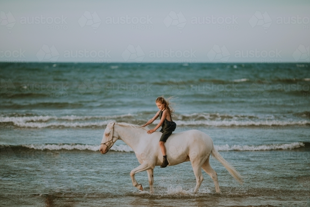 Girl riding horse in ocean waves - Australian Stock Image