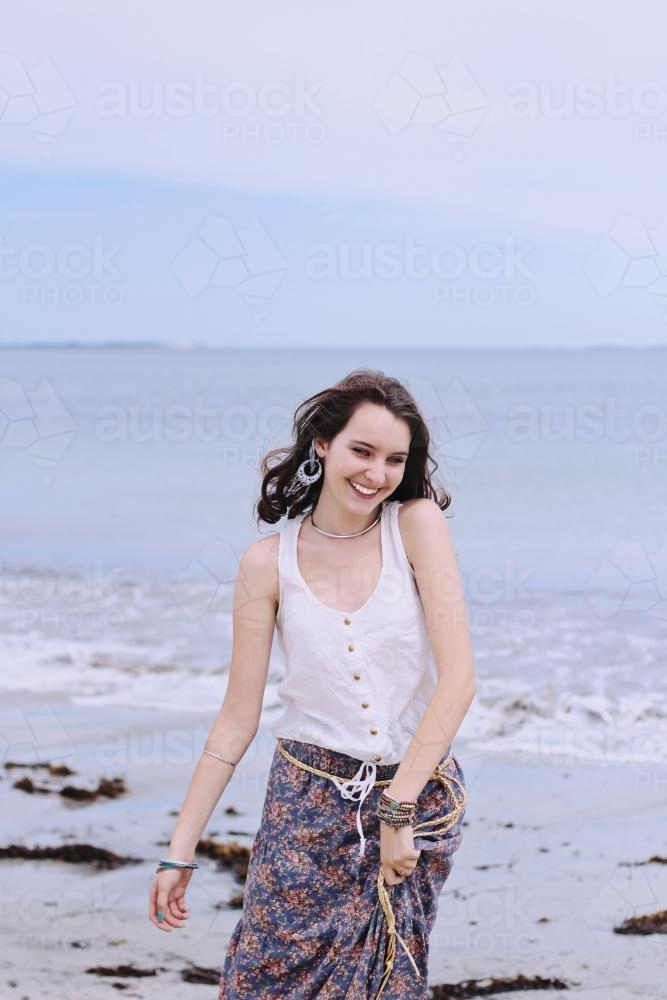 girl smiling at the beach in the winter sunset - Australian Stock Image