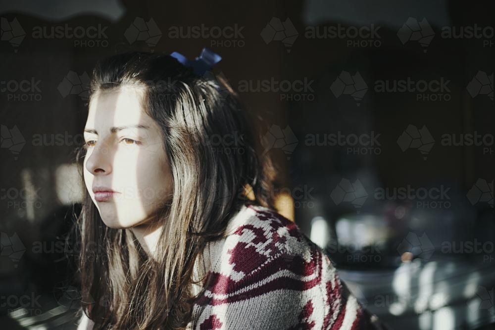 Girl standing in a darkened room illuminated by a sliver of window light - Australian Stock Image